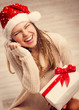 Xmas party celebration. Laughing Santa girl with present box