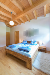 vertical shot of wooden bed in bedroom at timber house