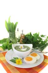grüne Kräutersuppe mit Eiern und Sahneklecks