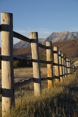 Wood fence line with autumn foliage on mountains