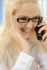 Frau mit Hornbrille telefoniert und lacht