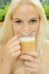 Frau trinkt Milchkaffee aus Trinkglas