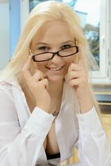 Blonde Frau richtet Brille