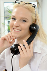 Sekretärin mit Brille beim Telefonieren