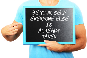 Man holding blackboard in hands and pointing the word BE YOUR SE