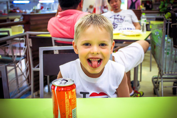 boy in a cafe showing tongue teased