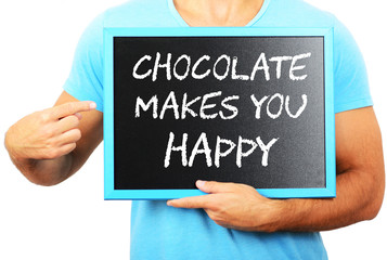 Man holding blackboard in hands and pointing the word CHOCOLATE