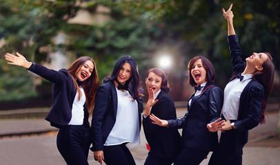group of stylish happy women on evening street