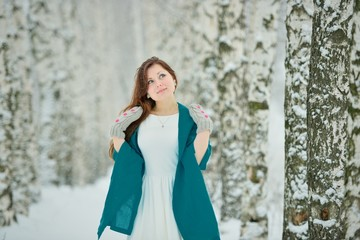 Woman in white dress in winter forest