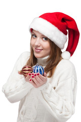 Beautiful woman wearing a santa hat smiling with christmas balls