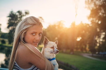Little chihuahua and blonde girl in the park