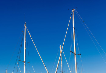 Detail shot of sailing boat poles (mainmasts) in marina.