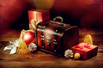 Chest, gifts and other christmas decoration on old wooden table