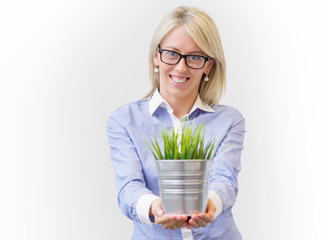 Young woman holding pot with decorative green grass