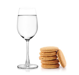 glass of water and cookies on white background