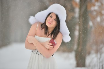 Woman in white dress with apple in winter forest
