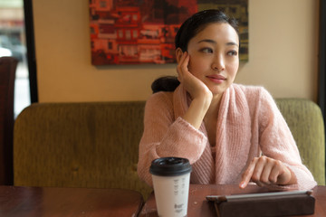 Young Asian Woman using tablet pc in a cafe