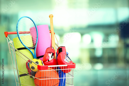 Shopping concept. Shopping cart with sport equipment - 71653410