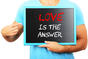 Man holding blackboard in hands and pointing the word LOVE IS TH