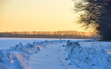 Landscape of a snow-covered field and sunset