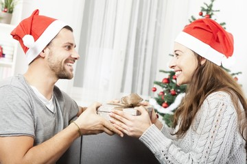 young couple makes a prenent for christmas