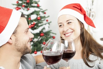 couple enjoy chistmas with wine on sofa