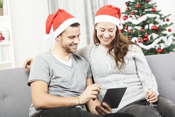 happy couple look on tablet pc for christmas