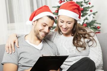happy couple write list for christmas on sofa