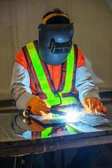 Worker welding the steel part by manual