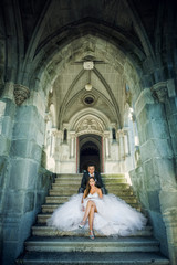 Noivos sentados nas escadas do castelo
