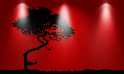 Silhouette of tree over red background with lights
