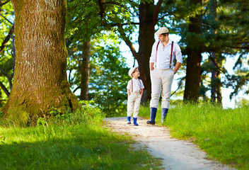 father and son walking rural path in forest