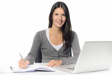 Freundliche junge Frau arbeitet am Schreibtisch