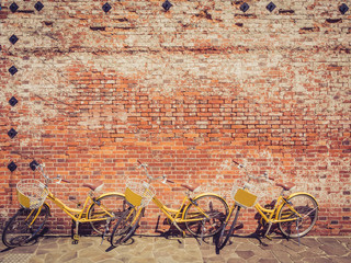 Three yellow bicycle against a brick wall with a retro filter