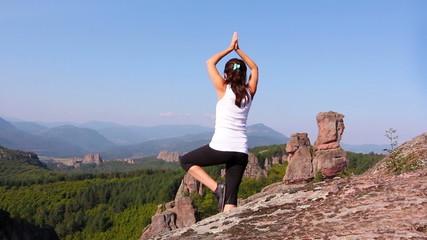 Woman doing yoga exercises on Belogradchik rocks