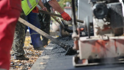 Asphalt paver applying asphalt on the way