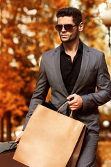 Handsome man in suit with shopping bags. Autumn.