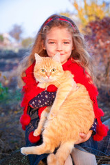 Little girl holding a red cat in autumn