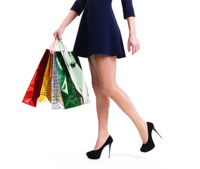 Woman in high heels with color shopping bags.