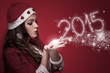 Woman in Santa costume blowing snowflakes and make New Year 2015