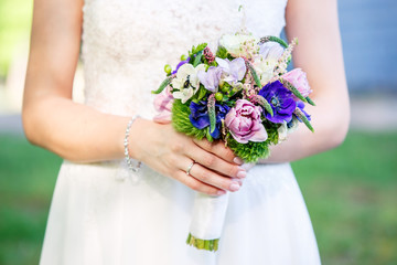 Beautiful bridal bouquet on a woman hands