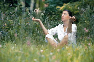 Beautiful young woman meditating on field