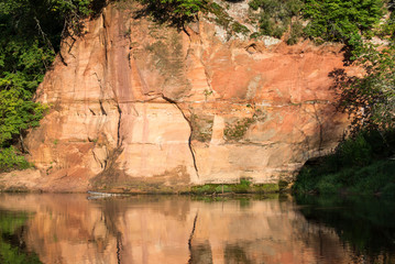 river with reflections in weater and sandstone cliffs