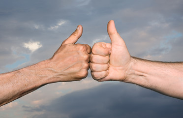 Two men bumping fists with thumbs up against sky with clouds