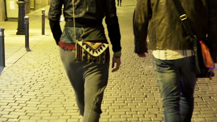 Couple grab, holding hands while walking in city at night