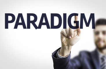 Business man pointing to transparent board with text: Paradigm