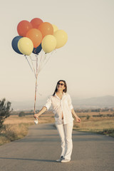 Pregnant woman with colorful ballons in her hand