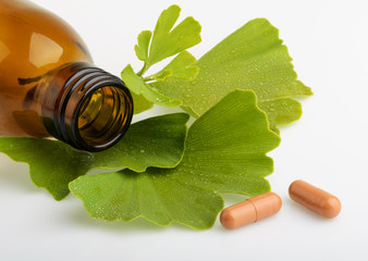 Ginkgo biloba leaves and medicine bottles with pills