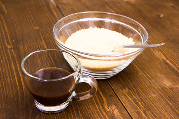 Coffee and bowl with brown sugar on wooden table