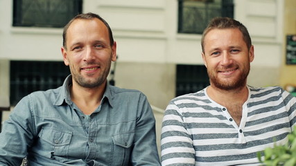 Two happy male friends sitting in cafe in the city